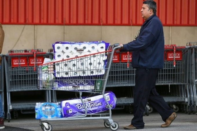 Một người đàn ông chất đầy giấy vệ sinh lên xe mua hàng tại một siêu thị ởMelbourne, bang Victoria, Australia, hôm 24/6. Ảnh: AFP.