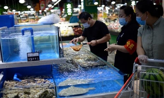 Khách hàng đeo khẩu trang lựa hải sản tại một siêu thi ở Trung Quốc ngày 17/6. Ảnh: Reuters.