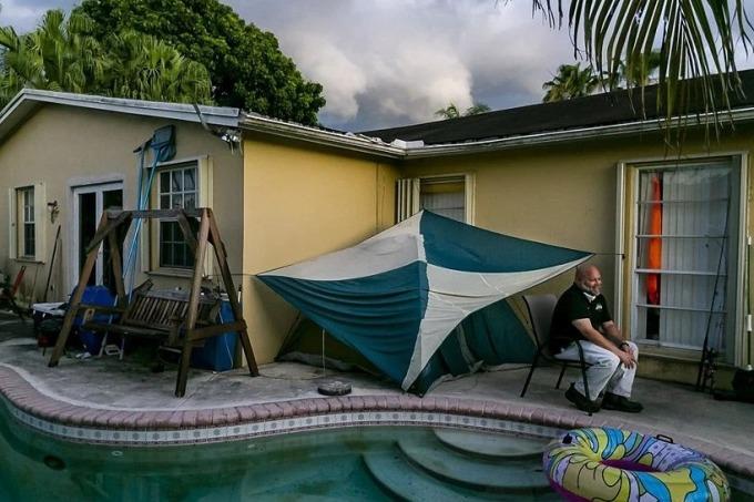 John Delgado bên cạnh túp lều sau sân nhà riêng ở Homestead, bang Florida, hôm 28/6. Ảnh: New York Times.