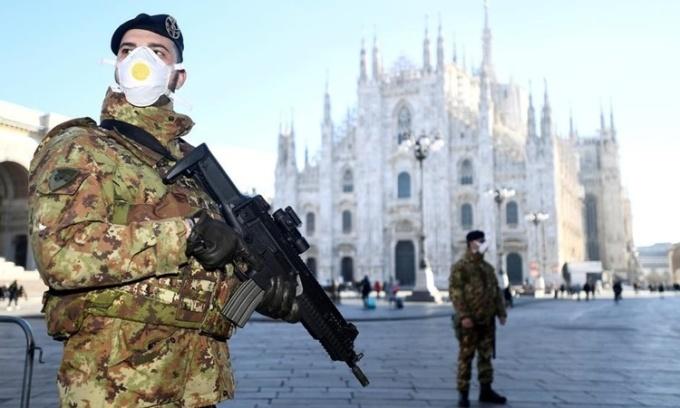 Sĩ quan quân đội đeo khẩu trang đứng gác bên ngoài Duomo ở Milan, Italy, ngày 24/2. Ảnh: Reuters.