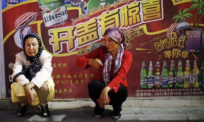 Hai phụ nữ dân tộc Duy Ngô Nhĩ ngồi trước một biển quảng cáo bia gần chợ ở Kashgar, Tân Cương tháng 8/2011. Ảnh: Reuters.