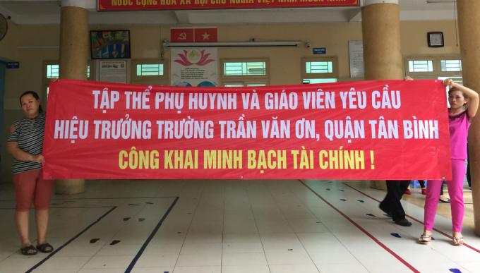 Phụ huynh trường Tiểu học Trần Văn Ơn (quận Tân Bình) căng băng rôn yêu cầu hiệu trưởng minh bạch thu chi tài chính, chiều 30/6. Ảnh: Mạnh Tùng.