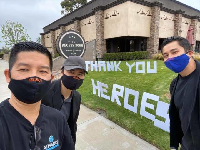 Việt Phạm (phải) và hai người bạn gốc Việt cùng tham gia các hoạt động đóng góp cho cộng đồng và y bác sĩ chống Covid-19 trước nhà hàng The Recess Room. Ảnh: Nhân vật cung cấp