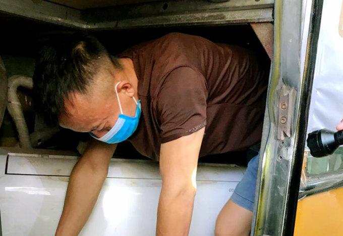 Một thanh niên chui ra khỏi hầm xe khách theo yêu cầu của nhà chức trách. Ảnh: Đức Hùng