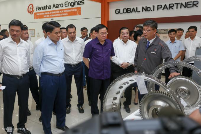 Ông Vương Đình Huệ (áo tím) cùng lãnh đạo TP Hà Nội và Bộ Khoa học Công nghệ thăm nhà máy sản xuất cấu kiện động cơ máy bay tại Khu CNC Hòa Lạc.