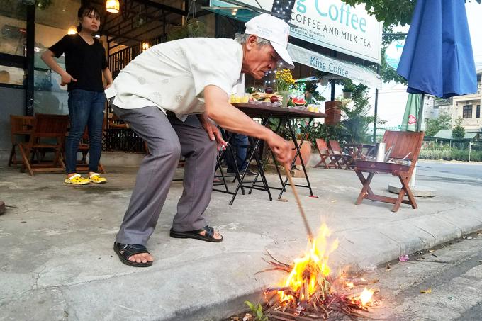 Ông Ngô Quang Ngữ đốt đống lửa trước mâm cỗ chiều ngày 23/5 âm lịch. Ảnh: Võ Thạnh
