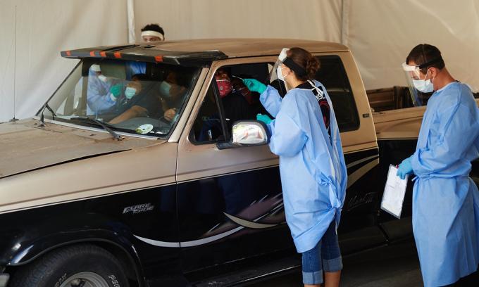 Nhân viên y tế lấy mẫu xét nghiệm nCoV cho tài xế tại Wimauma, bang Florida, hôm 9/7. Ảnh: NYTimes.
