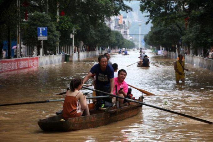 Người dân chèo thuyền di chuyển trong thành phố Liễu Châu, tỉnh Quảng Tây, hôm 11/7 vì lũ sau mưa lớn. Ảnh: Reuters.