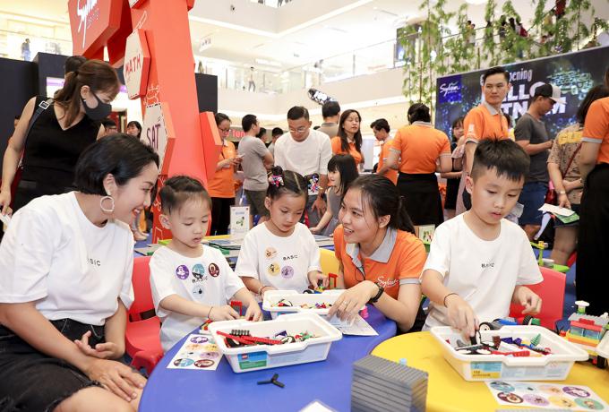 Các con của Ốc Thanh Vân đam mê trải nghiệm nhận sticker dán đầy áo tại ngày hội Sylvan Learning Việt Nam.