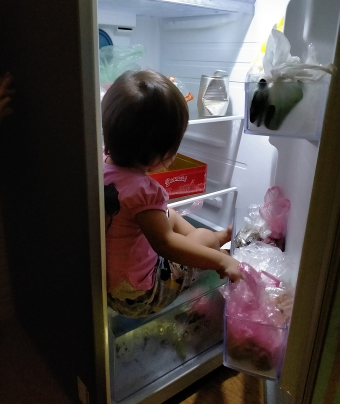 Một bé gái còn trèo tủ lạnh ngồi cho mát.