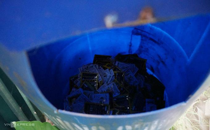 Những vỏ gói, túi thuốc bảo vệ thực vật đã dùng được anh Thành gom lại cho vào thùng ở góc ruộng. Ảnh: Hoàng Phương.