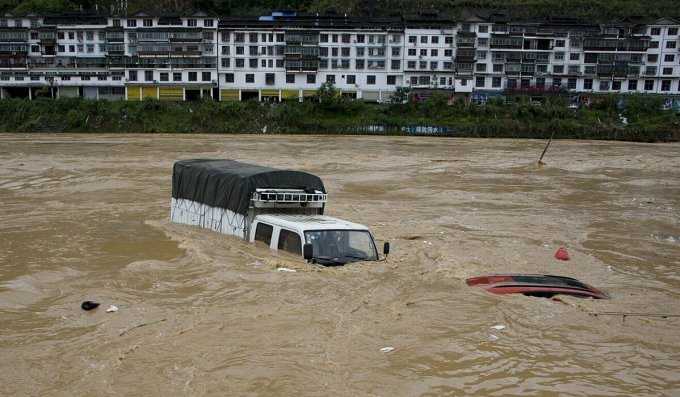 Xe cộ bị lũ nhấn chìm ở huyện Tòng Giang, tỉnh Quý Châu, hồi đầu tháng 6. Ảnh: SCMP