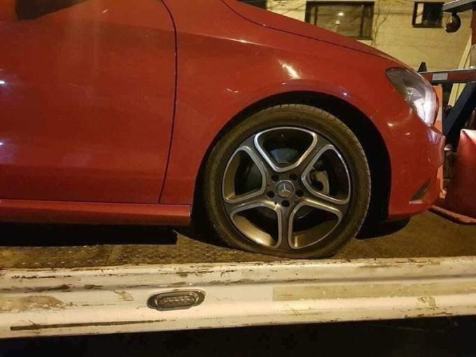 Ôtô màu đỏ nổ lốp và cần được cứu hộ.