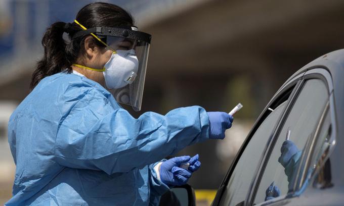 Nhân viên y tế lấy mẫu xét nghiệm nCoV tại một trạm lưu động ở thành phố San Diego, bang California, hôm 25/6. Ảnh: Reuters.