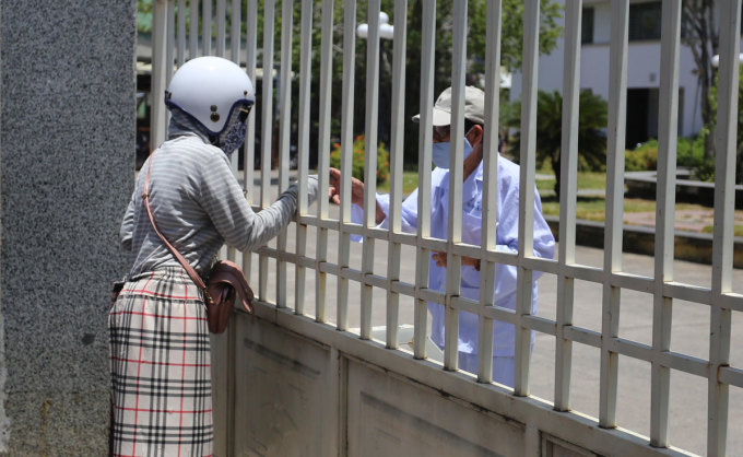 Bệnh viện Đà Nẵng bị phong tỏa, người nhà phải gửi đồ cho bệnh nhân qua cánh cổng sắt sáng 24/7. Ảnh: Đắc Thành.