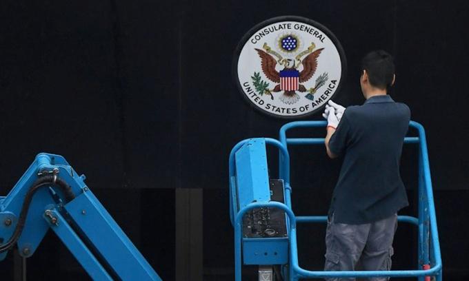 Nhân viên gỡ phù hiệu Mỹ tại lãnh sự quán ở Thành Đô, tỉnh Tứ Xuyên, hôm 25/7. Ảnh: AFP.