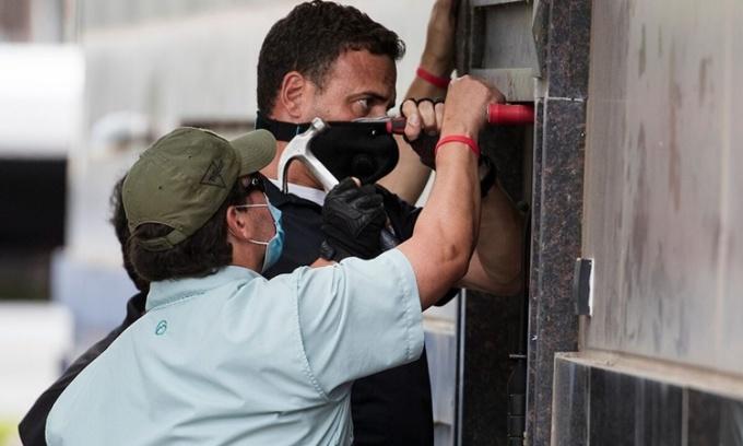 Những người được cho là quan chức thực thi pháp luật Mỹ phá cửa Tổng lãnh sự quán Trung Quốc ở Houston, Texas, ngày 24/7. Ảnh: AP.