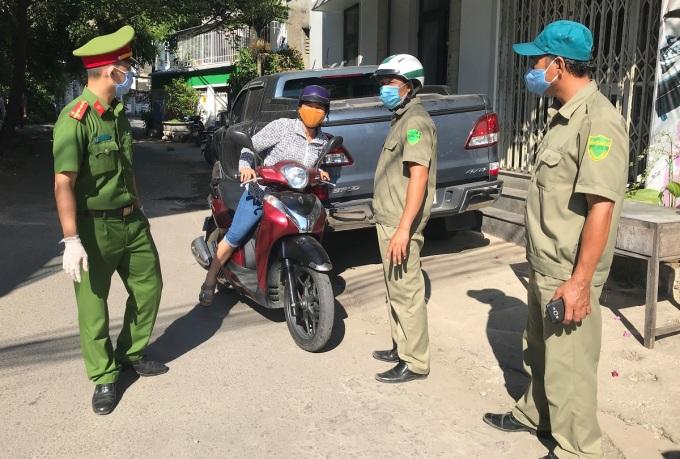 Lực lượng chức năng yêu cầu người dân không ra ngoài khu cách ly. Ảnh: Phạm Linh.
