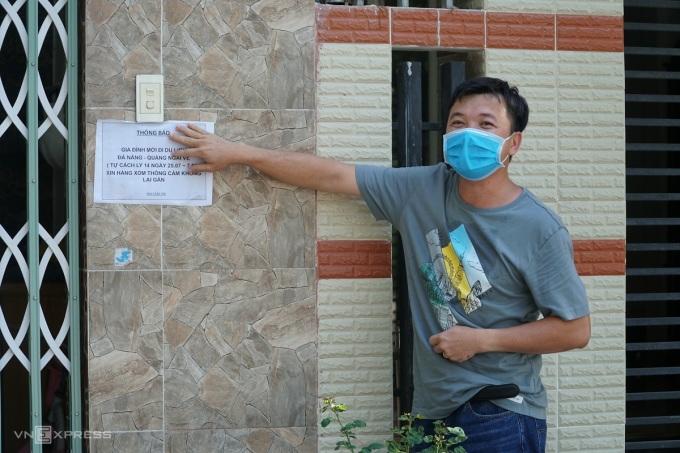 Anh Trình dán lại thông báo tự cách ly ở nhà anh Mãn sau khi giây thông báo  bị gió thổi mất kết dính. Ảnh: Phạm Linh.