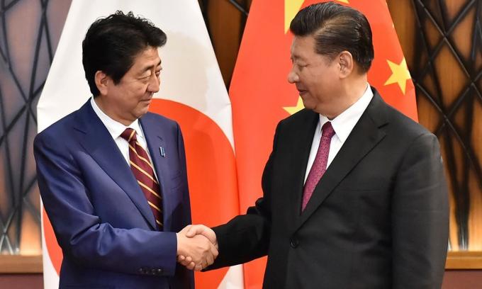 Thủ tướng Shinzo Abe (trái) bắt tay Chủ tịch Tập Cận Bình tại hội nghị APEC tại Việt Nam, hồi tháng 11/2017. Ảnh: AP.
