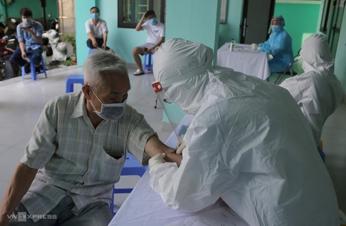 Nhân viên y tế phường Yên Hòa, quận Cầu Giấy lấy mẫu máu xét nghiệm cho người về từ Đà Nẵng ngày 30/7. Ảnh: Tất Định.