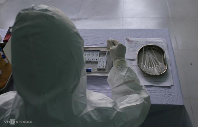 Nhân viên y tế đưa mẫu máu vào bộ xét nghiệm nhanh nCoV. Ảnh: Tất Định.