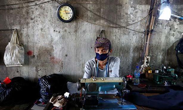Một thợ may đeo khẩu trang chống Covid-19 tại Jakarta, Indonesia, hôm 22/7. Ảnh: Reuters.