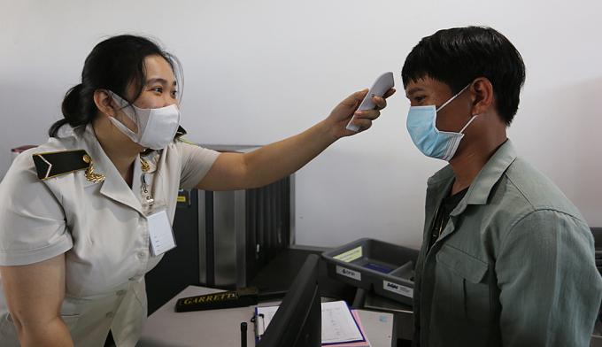 Nhân viên an ninh sân bay Chu Lai, Quảng Nam, đo thân nhiệt cho khách lên máy bay sáng 28/7. Ảnh: Đắc Thành.