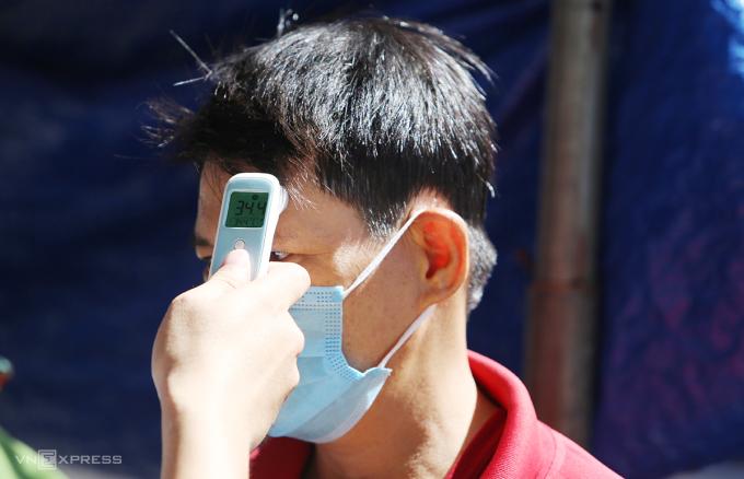 Lực lượng chức năng thị xã Điện Bàn đo thân nhiệt đi qua chốt kiểm dịch. Ảnh: Đắc Thành.