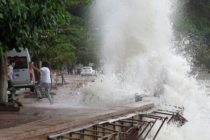 Nữ khách mon men ra bờ kè chụp ảnh selfile bỏ chạy khi bị cả cột sóng nước cao tới 6m độ sập xuống đầu. Ảnh: Giang Chinh