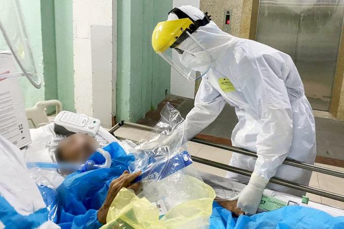 Nhân viên y tế thay người nhà chăm sóc cho bệnh nhân tại Bệnh viện Đà Nẵng. Ảnh: Hà Thu.