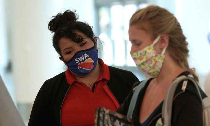 Nhân viên hãng hàng không và hành khách tại sân bay Los Angeles hồi tháng 5. Ảnh: Reuters.