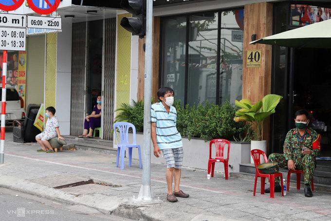 Nhiều cư dân trong khu cách ly trên đường Nguyễn Thị Minh Khai ra vỉa hè hỏi han các chiến sĩ làm nhiệm vụ gác chắn. Ảnh: Nguyễn Đông.