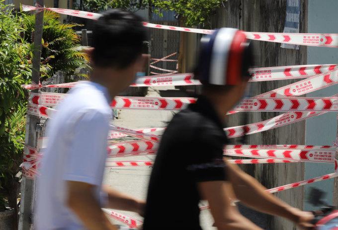 Người dân đi ngang một khu dân cư bị phong toả vì có người mắc nɔoʌ, ngày 28/7. Ảnh: Nguyễn Đông