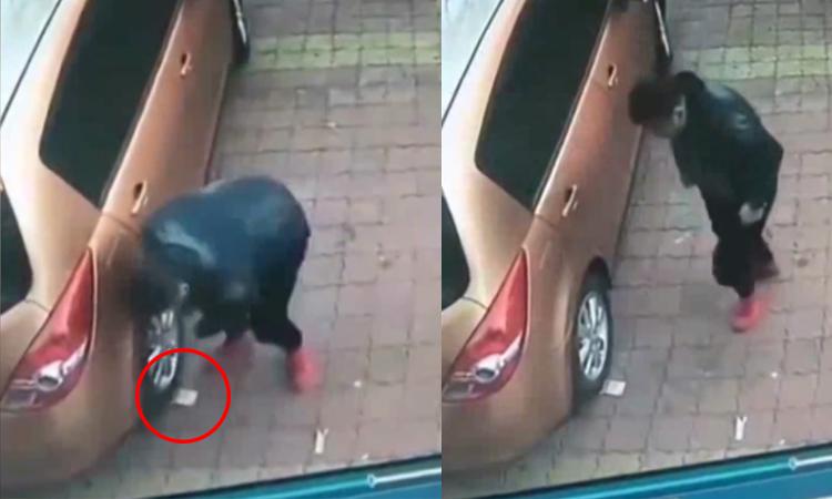 Người đàn ông loay hoay nhặt tiền dưới bánh ôtô