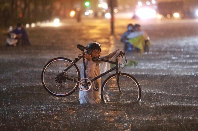 Người dân bì bõm vác xe máy qua rốn ngập Nguyễn Hữu Cảnh tối 6/8. Ảnh: Hữu Khoa - Quỳnh Trần.