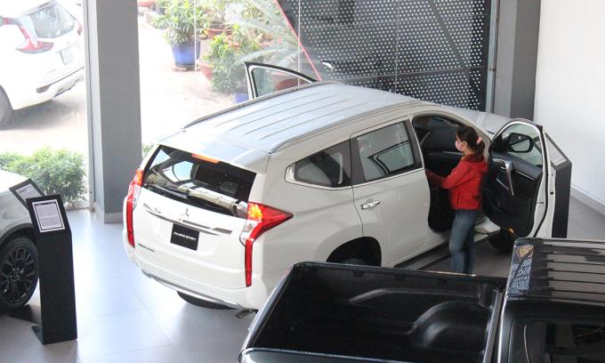 Khách hàng tham khảo một mẫu Pajero Sport (màu trắng) tại đại lý ở TP HCM. Ảnh: Phạm Trung