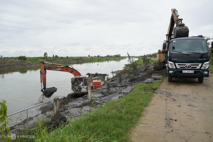 Máy xúc gia cố các đoạn đê bị sạt lở tại hồ Kênh Lấp hôm 6/8. Ảnh: Hoàng Nam