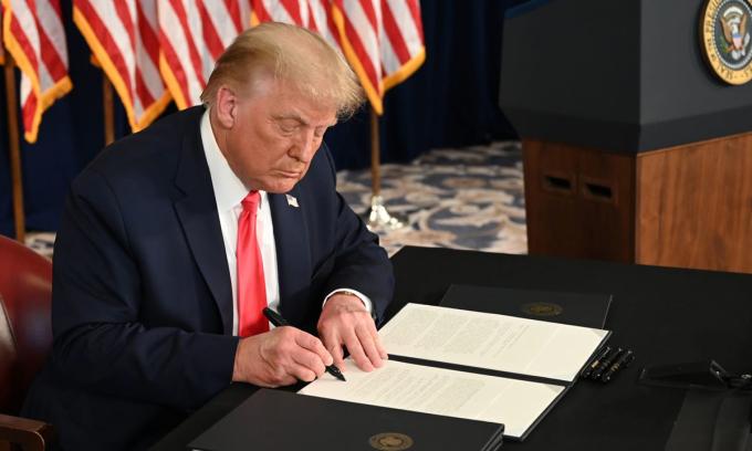 Tổng thống Mỹ Donald Trump ký sắc lệnh gia hạn cứu trợ kinh tế trong cuộc họp báo ở New Jersey hôm 8/8. Ảnh: AFP.
