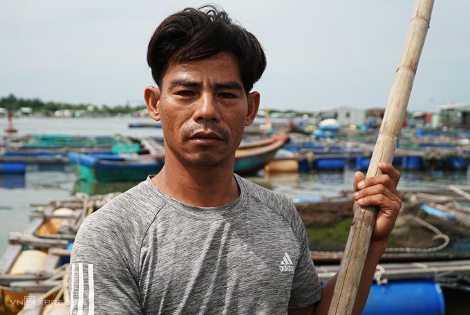 Ông Phan Quốc Toàn đang cầm vợt để vớt số cá chết nổi lềnh bềnh trong lồng. Ảnh: Trường Hà.