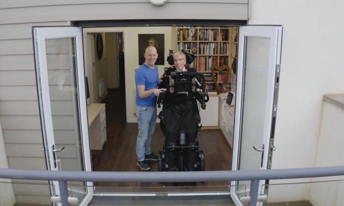 Tiến sĩ Scott-Morgan (phải) đứng bên cạnh bạn đời  Francis ở nhà riêng tại phía nam hạt Devon, Anh. Ảnh: Sugar Films.