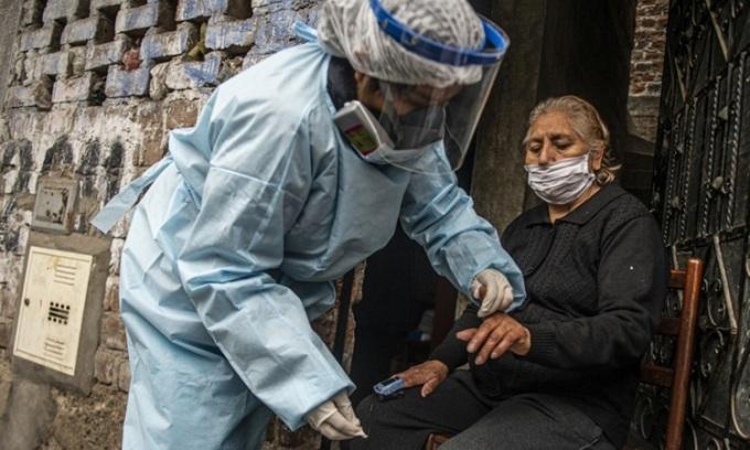 Nhân viên Bộ Y tế Peru kiểm tra và xét nghiệm Covid-19 cho một phụ nữ ở thủ đô Lima hôm 20/8. Ảnh: AFP.