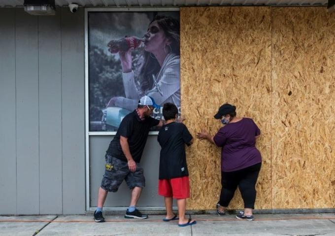 Người dân gia cố cửa hàng ở Hồ Charles, Louisiana, hôm 26/8. Ảnh: AFP.