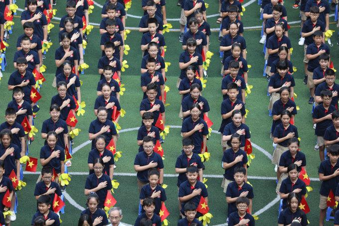 Học sinh trường Marie Curie chào cờ, hát Quốc ca trong lễ khai giảng sáng 5/9. Ảnh: Ngọc Thành