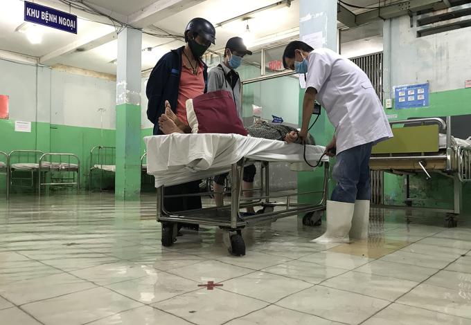 Bác sĩ phải mang ủng khám cho bệnh nhân. Ảnh: Đình Văn.