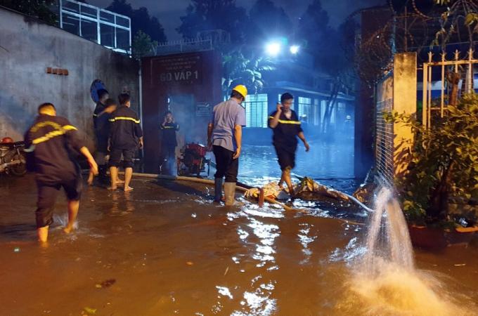 Cảnh sát dùng máy bơm hút nước trong trạm biến áp ra ngoài. Ảnh: Đình Văn.