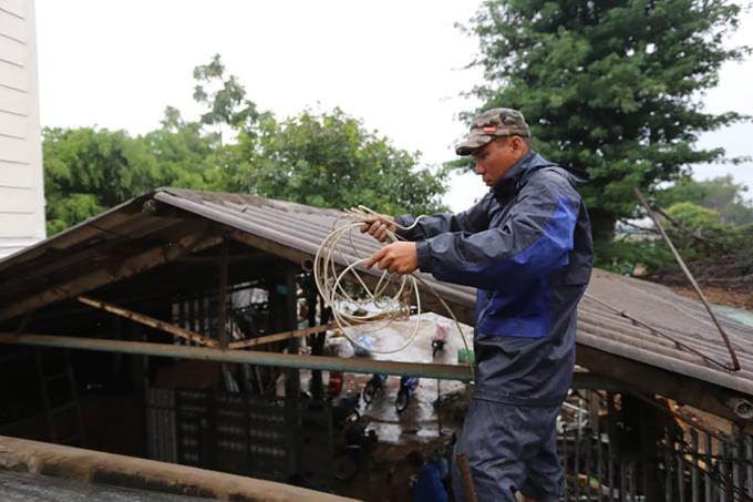 Anh Cao Văn Minh, xã Tam Đàn, huyện Phú Ninh, Quảng Nam dùng dây cáp chằng chống mái nhà phòng chống bão sáng 17/9. Ảnh: Đắc Thành.