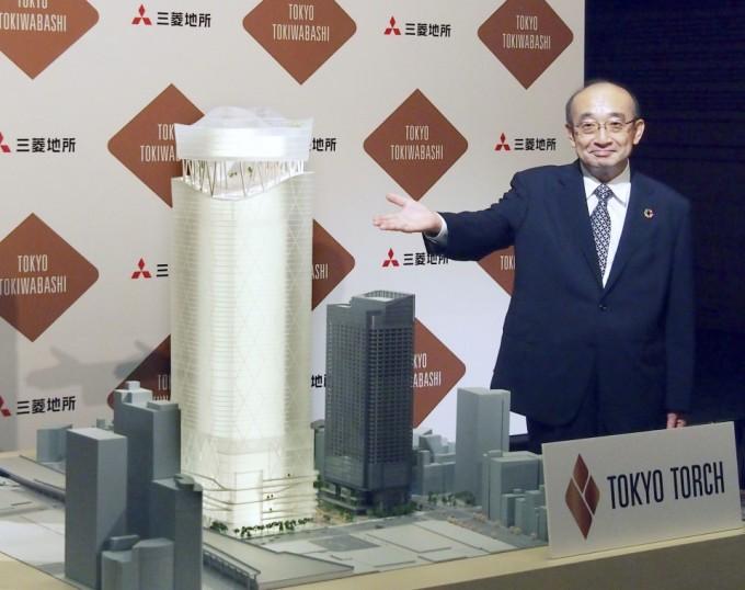 Chủ tịch công ty bất động sản Mitsubishi Junichi Yoshida bên mô hình tòa tháp cao nhất Nhật Bản, Torch Tower, tại họp báo ngày 17/9. Ảnh: Kyodo.