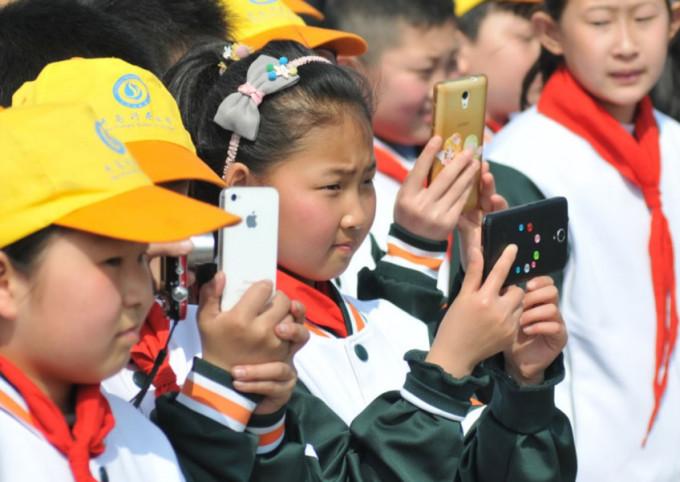 Học sinh tiểu học Trung Quốc dùng điện thoại chụp ảnh trong một hoạt động ngoại khóa hồi năm 2018 ở thành phố Thanh Đảo, tỉnh Sơn Đông. Ảnh: China Daily/Asia News Network.