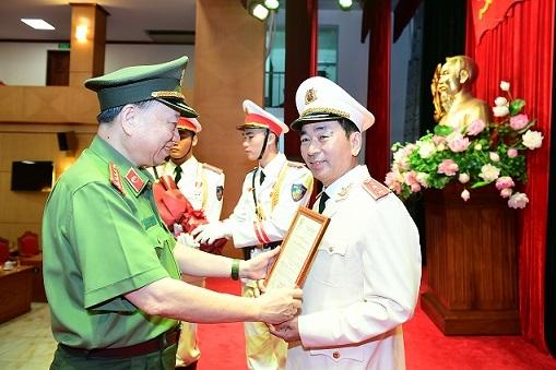 Bộ trưởng Công an Tô Lâm trao quyết định thăng cấp bậc hàm từ Thiếu tướng lên Trung tướng cho Thứ trưởng Trần Quốc Tỏ. Ảnh: Bộ Công an